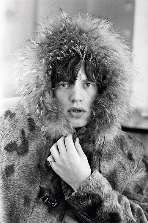 Rolling Stones singer Mick Jagger posing in a fur parka, with a fur trimmed hood, 1964.